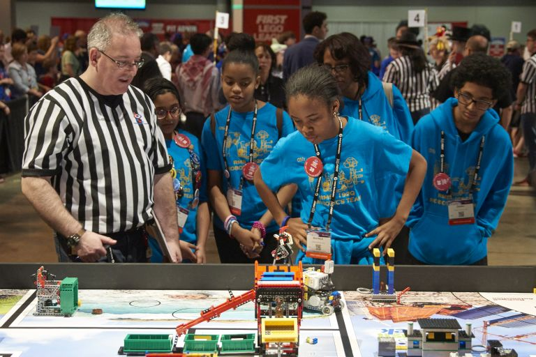 Kids and referee at a FIRST LEGO League tournament.