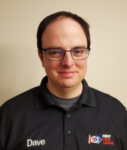 Photo of Dave Baran smiling. He has brown hair and glasses and wears a black polo shirt embroidered with his name and the FIRST LEGO League logo.