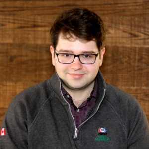 photo of Stephen Swartzentruber, who has brown hair and glasses and is wearing a grey FIRST LEGO League Explore half-zip crewneck